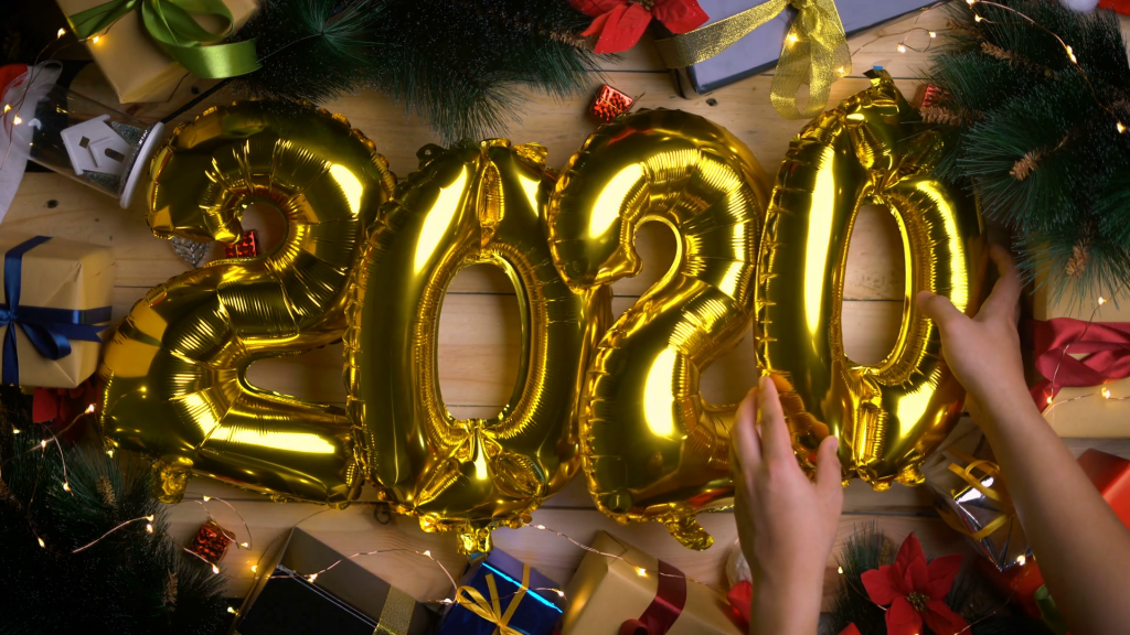 videoblocks people decorating 2020 golden balloon between christmas decoration top view howqqt6bsx thumbnail full03 1024x576